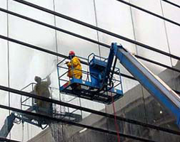 Workers on a lift performing quality checks on a glass wall installation.
